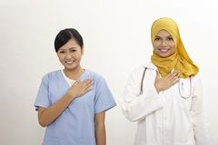 Doctor and nurse. Asian nurse and doctor with welcome hand sign on the white background Stock Images