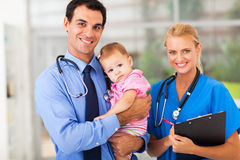 Doctor nurse baby. Smiling pediatric doctor and nurse with baby girl Royalty Free Stock Photo