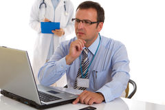 Doctor with nurse in the background Stock Photos