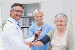 Doctor and nurse checking patients blood pressure. Portrait of happy doctor and nurse checking senior patients blood pressure in clinic Royalty Free Stock Photography