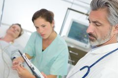 Doctor and nurse with clipboards visiting patient woman at hospital royalty free stock photography