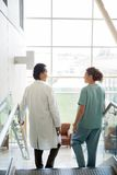 Doctor And Nurse Conversing While Walking Down Royalty Free Stock Photo