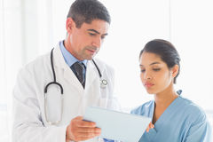 Doctor and nurse discussing over digital tablet Royalty Free Stock Photos