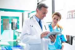 Doctor and nurse discussing over digital tablet Stock Photo