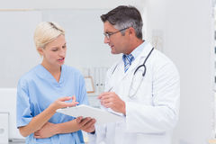 Doctor and nurse discussing over notes in clinic Stock Image