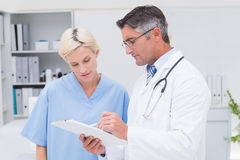 Doctor and nurse discussing over notes on clipboard Royalty Free Stock Images