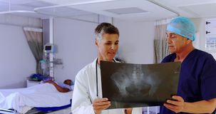 Doctor and nurse discussing over x-ray report 4k. Front view of Caucasian female doctor and male nurse discussing over x-ray report in the ward at hospital. They stock video footage