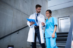 Doctor and nurse discussing over a report while climbing down stairs Royalty Free Stock Image
