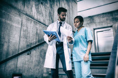 Doctor and nurse discussing over report while standing on stairs. In hospital Royalty Free Stock Photos