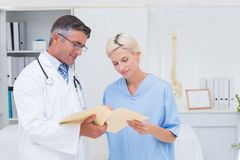 Doctor and nurse discussing over reports Stock Image