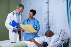 Doctor and nurse discussing report during visit in ward. Of hospital Stock Photos
