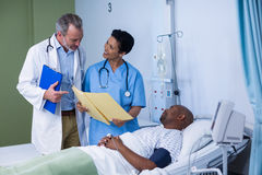 Doctor and nurse discussing report during visit in ward. Of hospital Stock Photography