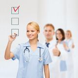 Doctor or nurse drawing checkmark into checkbox Stock Images
