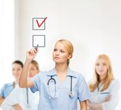 Doctor or nurse drawning checkmark into checkbox Royalty Free Stock Photo