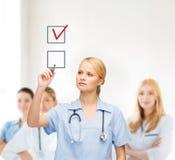 Doctor or nurse drawning checkmark into checkbox Royalty Free Stock Photo
