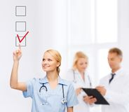 Doctor or nurse drawning checkmark into checkbox Stock Photography