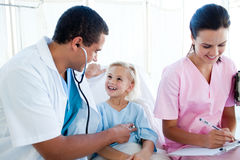 A doctor and a nurse examining a child patient