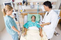 Doctor And Nurse Examining Critical Patient Stock Photo