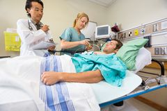 Doctor And Nurse Examining Patient In Hospital Stock Image