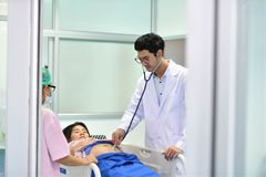 Doctor, nurse examining pregnant woman with stethoscope. Doctor, nurse examining pregnant women with stethoscope at maternity ward Stock Photography