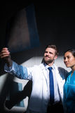 Doctor and nurse examining X-ray report. At the hospital premises Stock Photos