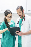 Doctor and nurse examining report of patient royalty free stock images
