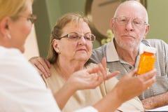 Doctor or Nurse Explaining Prescription Medicine to Senior Couple. Doctor or Nurse Explaining Prescription Medicine to Attentive Senior Couple stock photo