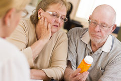 Doctor or Nurse Explaining Prescription Medicine to Senior Coupl Stock Images
