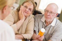Doctor or Nurse Explaining Prescription Medicine to Senior Coupl Stock Images
