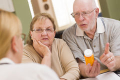 Doctor or Nurse Explaining Prescription Medicine to Senior Coupl Stock Photo
