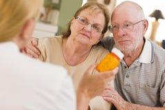 Doctor or Nurse Explaining Prescription Medicine to Senior Couple royalty free stock photography