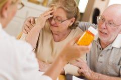 Doctor or Nurse Explaining Prescription Medicine to Senior Coupl Royalty Free Stock Photography