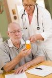 Doctor or Nurse Explaining Prescription Medicine to Senior Man stock images