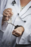 Doctor or Nurse In Handcuffs Wearing Lab Coat and Stethoscope Royalty Free Stock Photo
