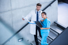Doctor and nurse holding medical report and climbing down stairs Stock Photo