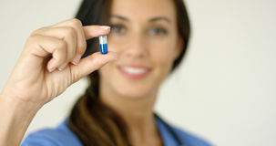 Doctor or nurse holding up a capsule Royalty Free Stock Images
