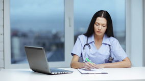 Doctor or nurse with laptop pc writing stock video