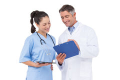 Doctor and nurse looking at clipboard Royalty Free Stock Photos