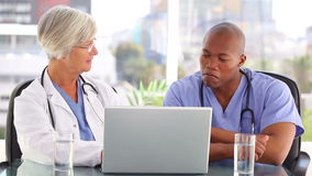 A doctor and a nurse looking at a laptop. In a bright office stock video
