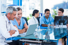 Doctor and nurse looking at laptop with colleagues behind Royalty Free Stock Photos