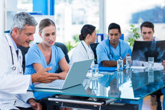 Doctor and nurse looking at laptop with colleagues behind Royalty Free Stock Photography
