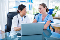 Doctor and nurse looking at laptop Stock Images