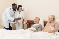A doctor and a nurse offer an elderly couple an apple, marshmallows and muffins to bed. Stock Photo