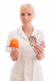 Doctor or nurse with orange and pills. Young doctor or nurse holding orange and pills on isolated white background stock images