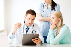 Doctor and nurse with patient in hospital stock images