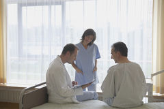 Doctor And Nurse With Patient In Hospital Room stock image
