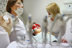 Doctor and nurse perform the procedure for dental treatment Stock Photos