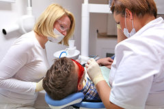 Doctor and nurse perform the procedure for dental treatment Royalty Free Stock Images
