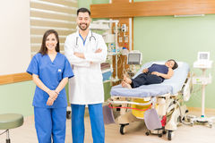 Doctor and nurse with a pregnant patient. Portrait of a handsome Hispanic doctor and beautiful nurse standing in a hospital room with a pregnant patient Stock Photography