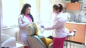 Doctor and nurse prepare female patient for dental procedure. Doctor and nurse prepare young female patient for dental procedure stock video footage
